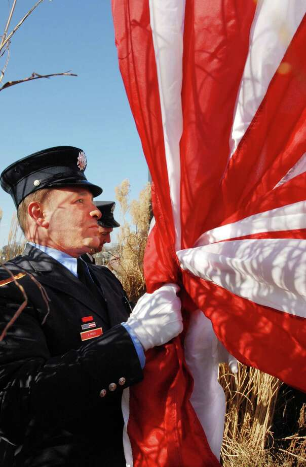 West Haven Firefighter Ken Prisco prepares the new flag to be raised during the 2006 Pearl Harbor Remebrance Day ceremonies at Bradley Point. Photo: Hearst Connecticut Media File