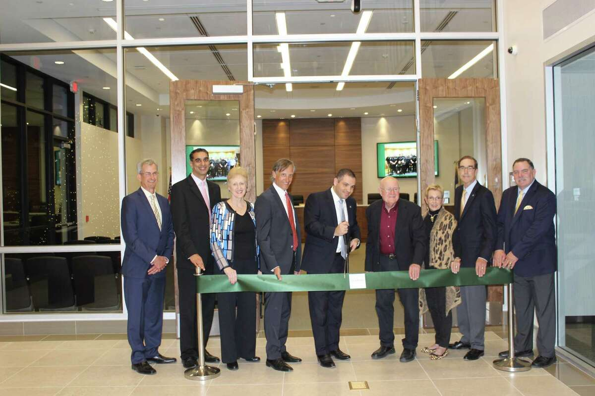 Bellaire City Manager Paul Hofmann (pictured from left), Council Members Neil Verma and Trisha Pollard, Mayor Pro Tem and Council Member Gus Pappas, Mayor Andrew Freidberg, Council Members Pat McLaughlan, Michael Fife and David Montague and former MayorPhil Nauert celebrate their first meeting in the new council chamber with a ribbon-cutting ceremony on Monday, Dec. 3.