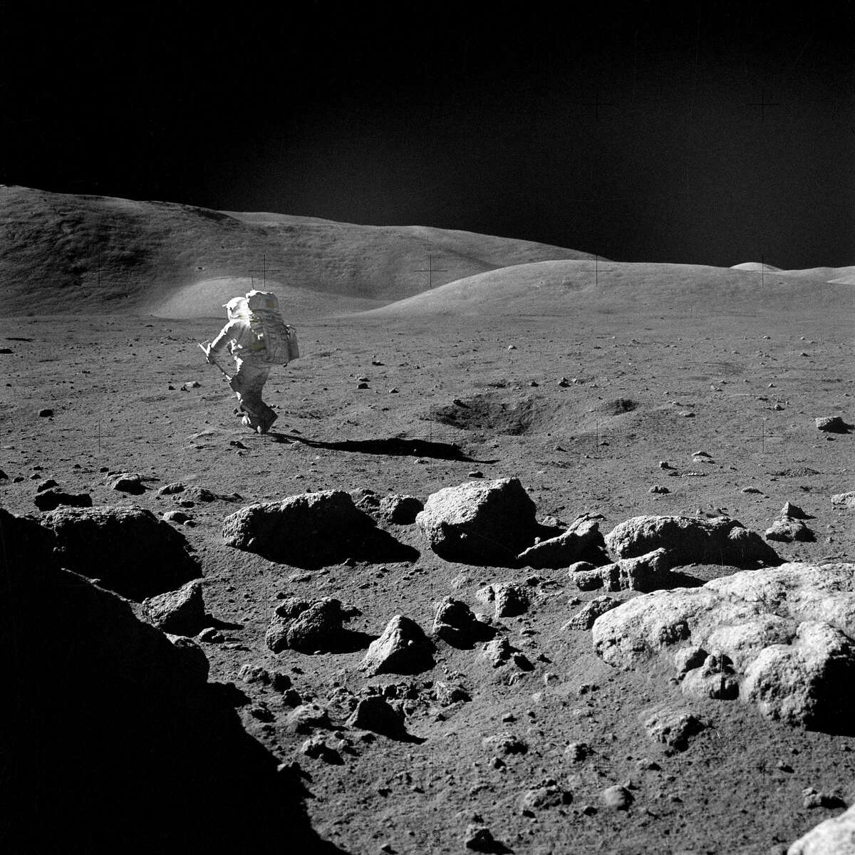 Harrison Schmitt heads for a selected rock on the lunar surface to retrieve the sample for study. The action was photographed by Apollo 17 crew commander, astronaut Eugene Cernan.