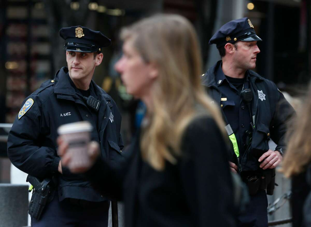 Police officers Alan Katz (left) and Chris Simpson patrol on foot at Powell and Market streets in San Francisco, Calif. on Tuesday, Dec. 4, 2018.
