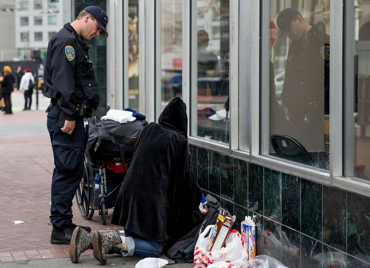 SFPD Officer Maher clears people sitting on the sidewalk as he walks through the Civic Center Plaza area with Officer Richmond in San Francisco, Calif. on Tuesday, Dec. 4, 2018.