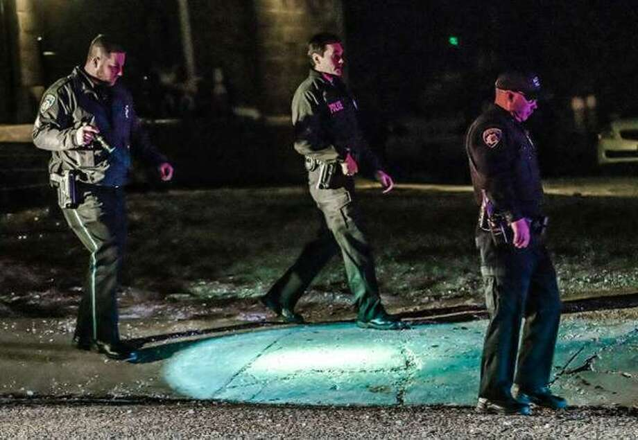 Alton police officers search the to the 800 block of Ridge Street last Thurday night after a man was shot during an altercation. A suspect in the shooting was charged Tuesday.