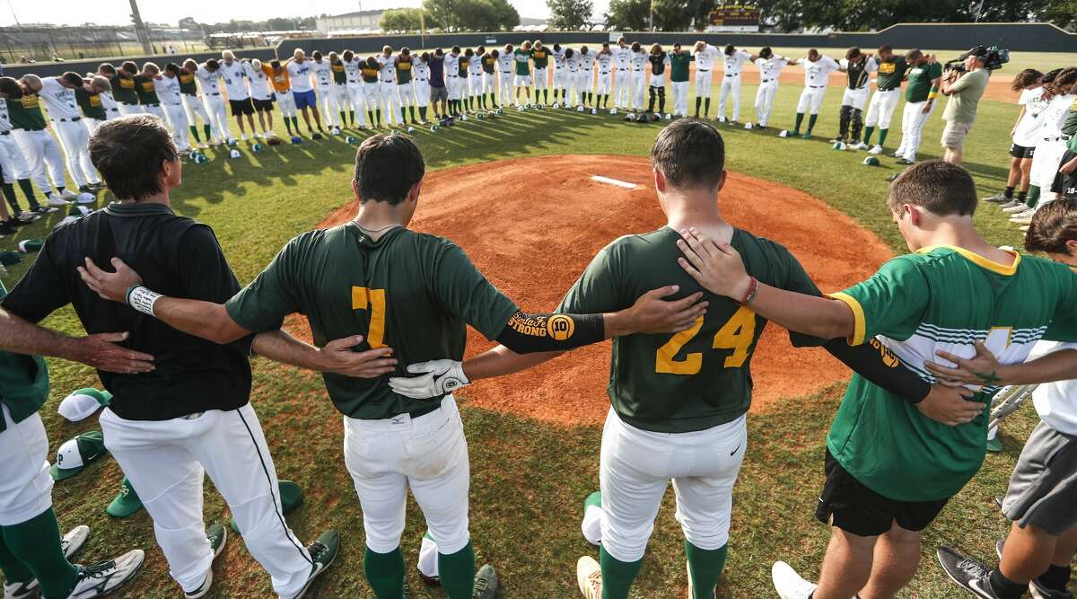 Santa Fe High School and Kingwood Park baseball players bow heads in prayer as they gather in the middle of the field before a Class 5A Region III playoff baseball game on Saturday, May 19, 2018, in Deer Park.