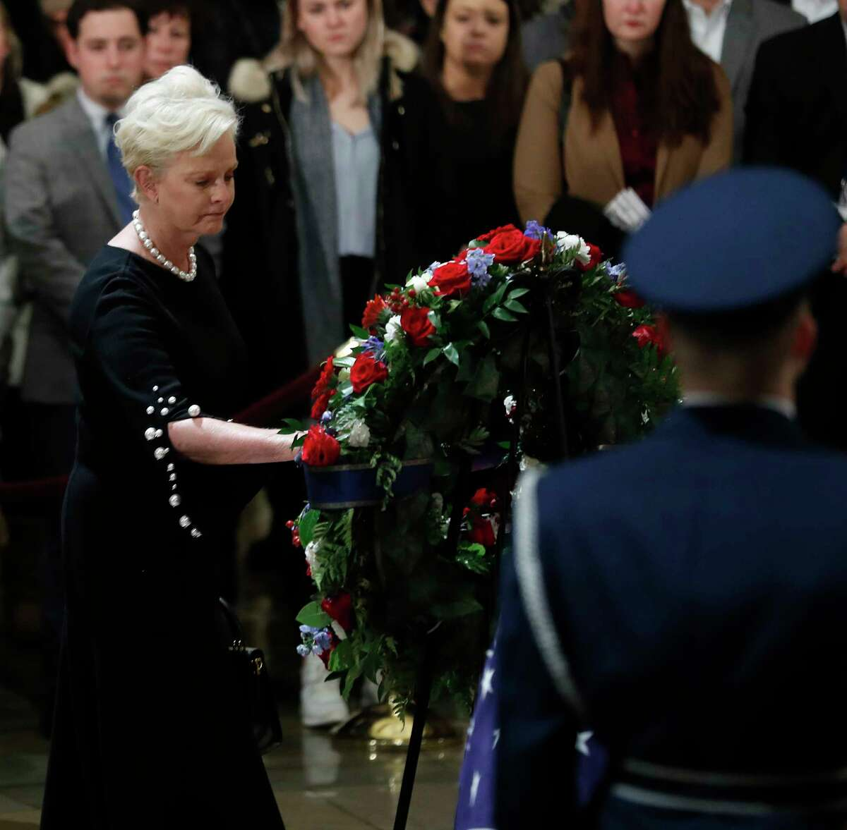 Cindy McCain, wife of John McCain places a kiss on a wreath as she paused near the casket of President George H.W. Bush while he laid in state at the United States Capitol Rotunda, Tuesday, Dec. 4, 2018, in Washington. Bush will lie in state in the Rotunda until Wednesday morning.