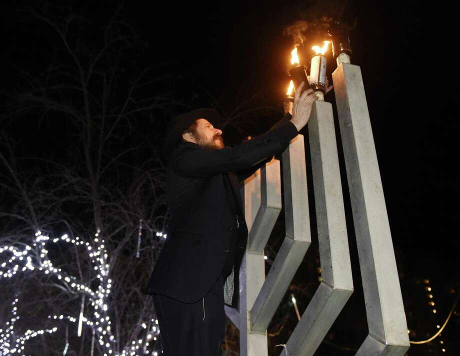 Rabbi Moshe Shemtov lights the menorah at Chabad of Stamford's Giant Menorah Lighting at Latham Park in Stamford, Conn. Tuesday, Dec. 4, 2018. Fairfield County's largest menorah was lit as folks enjoyed music, apple cider and latkes in a celebration on the third night of Hanukkah. Photo: Tyler Sizemore / Hearst Connecticut Media / Greenwich Time