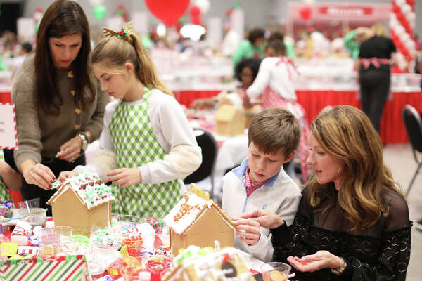 From left, Diane Ham, Anderson Ham, Ross Blackburn and Kelly Blackburn decorate gingerbread houses during the Gingerbread Haven event benefitting Midland Fair Havens, Dec. 4, 2018, at Horseshoe Arena. James Durbin/Reporter-Telegram