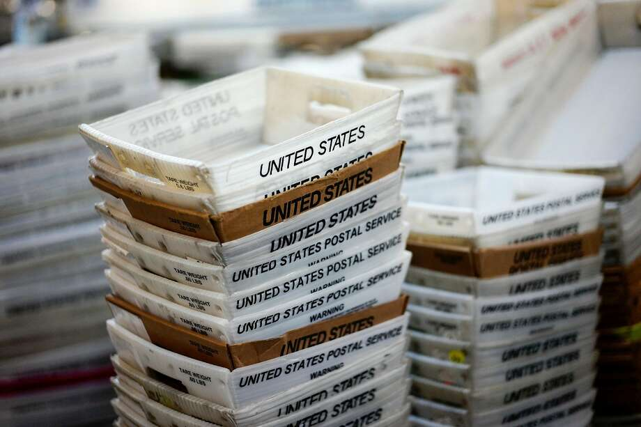 """FILE- In this Dec. 14, 2017, file photo, boxes for sorted mail are stacked at the main post office in Omaha, Neb. A task force created by President Donald Trump to evaluate ways to stem billions of dollars in losses at the U.S. Postal Service is suggesting a range of options, including proposals that could significantly boost the cost of sending non-essential mail. The report recommended that the Postal Service develop a new pricing model that would remove current price caps and charge market-based prices for both mail and packages that were not deemed to be """"essential postal services."""". (AP Photo/Nati Harnik, File) Photo: Nati Harnik, Associated Press"""