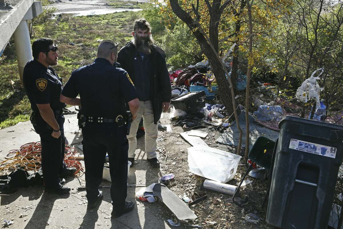 """Leland Ray Wood, 51, formerly of Lancaster, California, talks with San Antonio Fear Free Environment Officers Johnny Perez, left, and Elliott Valdez, at an encampment by a bridge on Culebra Road, Tuesday, Dec. 4, 2018. San Antonio City Council District 6 Representative Greg Brockhouse organized the outreach providing food and jackets to the homeless. City of San Antonio Homeless Services Division, Haven for Hope and Department of Veteran Affairs personnel joined in the effort. ?'All I need is warm gloves,?"""" said Wood, who has been homeless for over 10 years."""