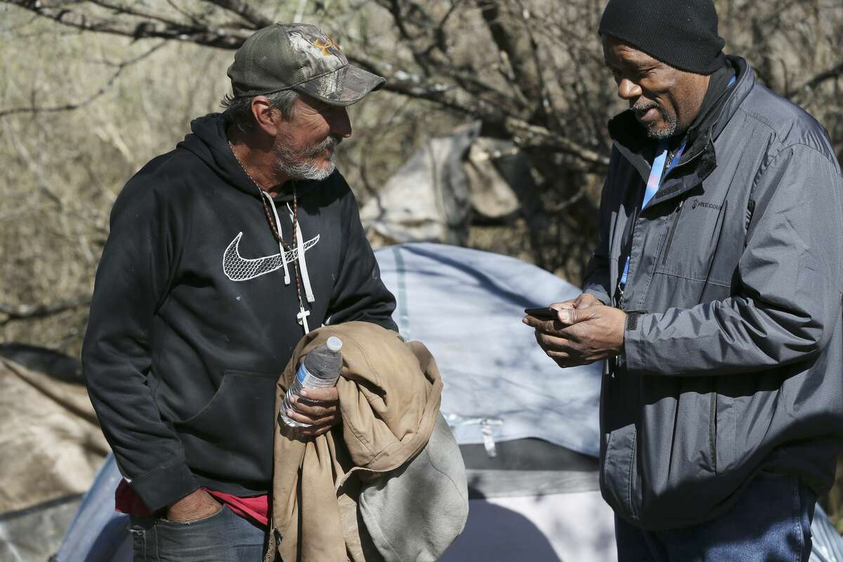 Haven for Hope Director of Outreach Ron Brown, right, signs up Mike Stephens for detox during a visit to a homeless encampment near the intersection of Potranco Road and State Highway 151, Tuesday, Dec. 4, 2018.