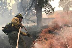 A Wildfire Defense Systems firefighter applies a vegetative retardant fireline to a property in the Mendocino Complex wildfire earlier this year near Largo, Calif.