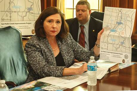 San Antonio River Authority General Manager Suzanne Scott, with engineer Russell Persyn in the background, shows a map of proposed improvements to San Pedro Creek in 2013.