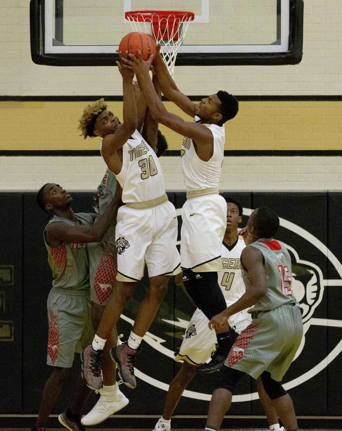 Conroe guards Keith Edmond (30) and Michael Phoenix (3) go for a reobund during the first quarter of a non-district high school basketball game at Conroe High School, Tuesday, Dec. 4, 2018, in Conroe.