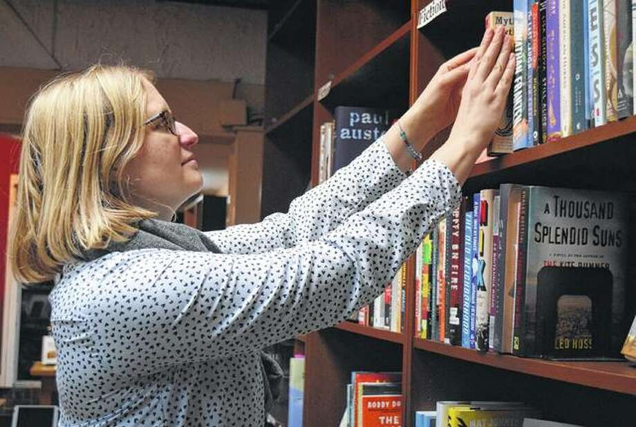 Jessica Gale stocks books on the shelves of Our Town Books Tuesday night. Photo: Samantha McDaniel-Ogletree | Journal-Courier