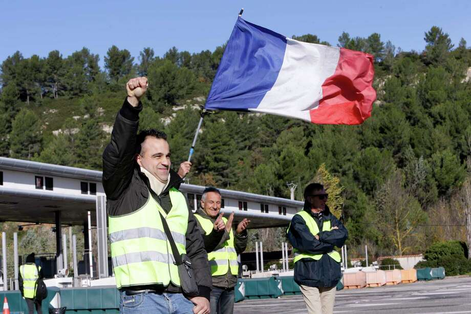 A demonstrators wearing a yellow vest clenches his fist as protesters open the toll gates on a motorway near Aix-en-Provence, southeastern France, Tuesday, Dec. 4, 2018. French Prime Minister Edouard Philippe announced a suspension of fuel tax hikes Tuesday, a major U-turn in an effort to appease a protest movement that has radicalized and plunged Paris into chaos last weekend. (AP Photo/Claude Paris) Photo: Claude Paris / Copyright 2018 The Associated Press. All rights reserved.