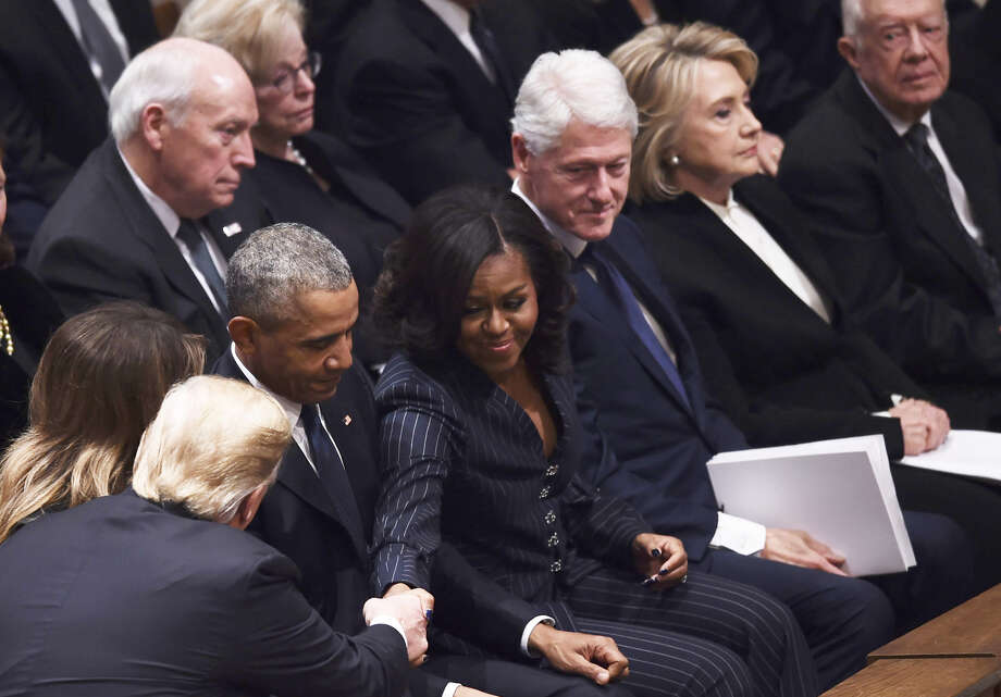 President Donald Trump shakes hands as former US President Barack Obama, former US First Lady Michelle Obama, former US President Bill Clinton, former First Lady Hillary Clinton, and former US President Jimmy Carter sit before the funeral service for former US President George H. W. Bush at the National Cathedral in Washington, DC on December 5, 2018. Photo: BRENDAN SMIALOWSKI, AFP/Getty Images