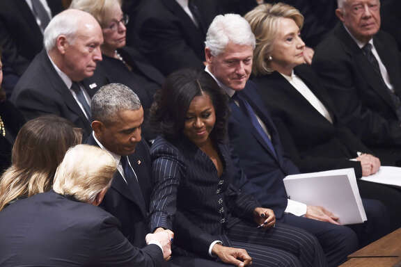 (Front L-R)US President Donald Trump shakes hands as former US President Barack Obama, former US First Lady Michelle Obama, former US President Bill Clinton, former First Lady Hillary Clinton, and former US President Jimmy Carter sit before the funeral service for former US President George H. W. Bush at the National Cathedral in Washington, DC on December 5, 2018. (Photo by Brendan SMIALOWSKI / AFP)BRENDAN SMIALOWSKI/AFP/Getty Images