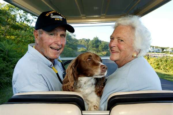 Former U.S. president George H. W. Bush and wife, Barbara Bush, cruise in the back of a golf cart with their dog Millie at their home at Walker's Point August 25, 2004 in Kennebunkport, Maine.
