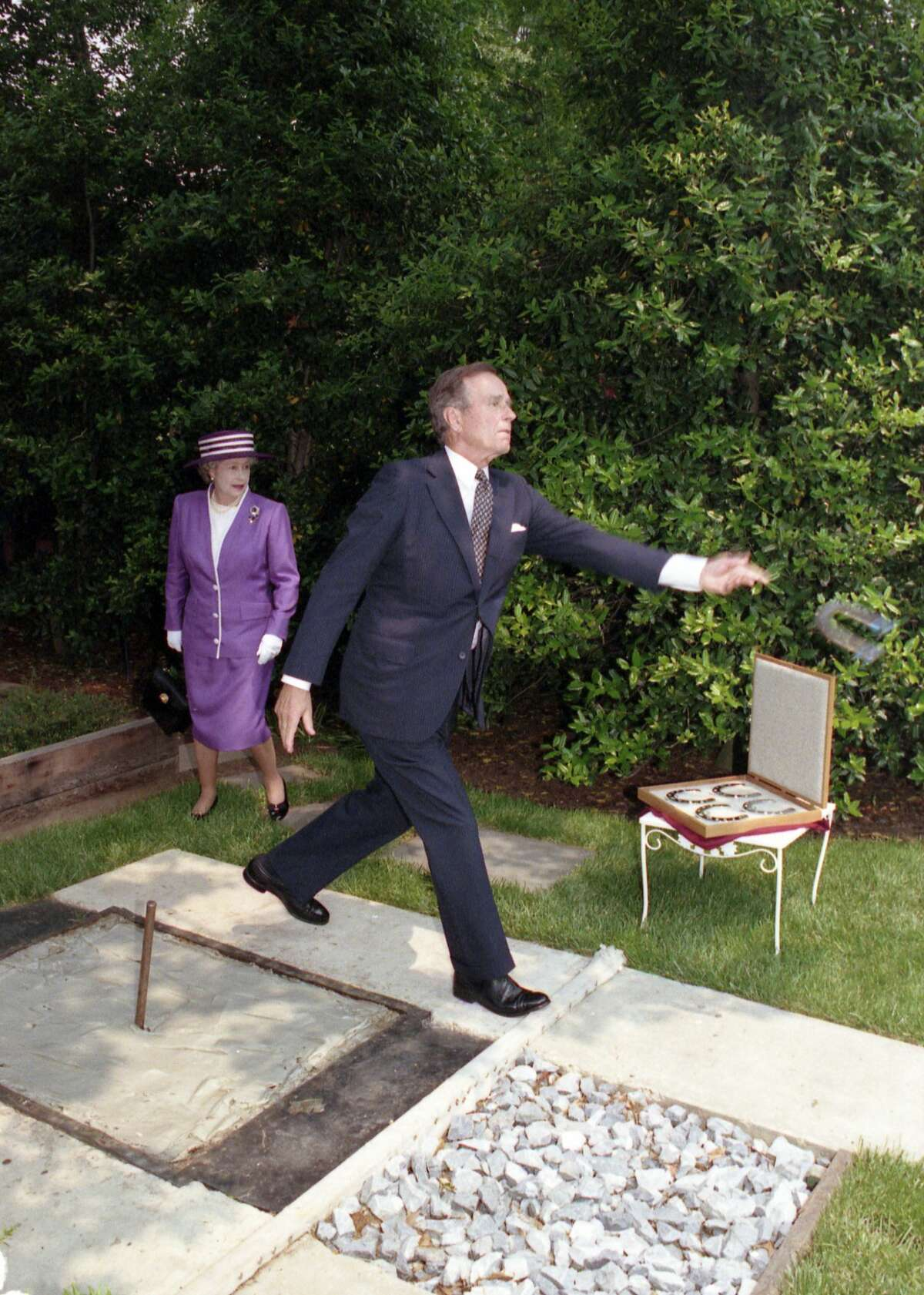 President Bush demonstrates his horseshoe pitching abilities after Queen Elizabeth of Great Britain presents him four silver horseshoes engraved