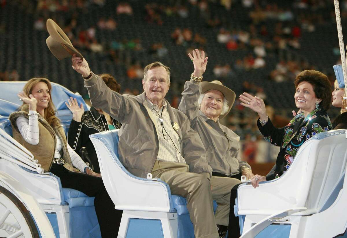 President George H.W. Bush and his wife Barbara (center rear) wave to the crowd during the grand entry parade at the Houston Livestock Show and Rodeo at Reliant Stadium in Houston, Texas March 1, 2007.