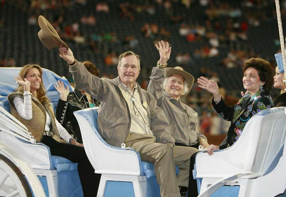 President George H.W. Bush and his wife Barbara (center rear) wave to the crowd during the grand entry parade at the Houston Livestock Show and Rodeo at Reliant Stadium in Houston, Texas March 1, 2007. Photo: James Nielsen/Houston Chronicle