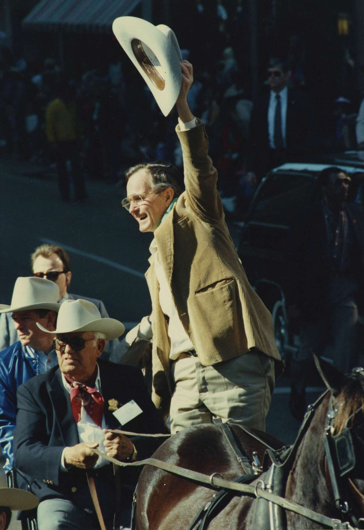 Vice President George Bush, Republican candidate for president, serves as grand marshal of the Houston Livestock Show and Rodeo parade. Bush waves his cowboy hat to parade goers in downtown Houston, Saturday, Feb, 20, 1988.