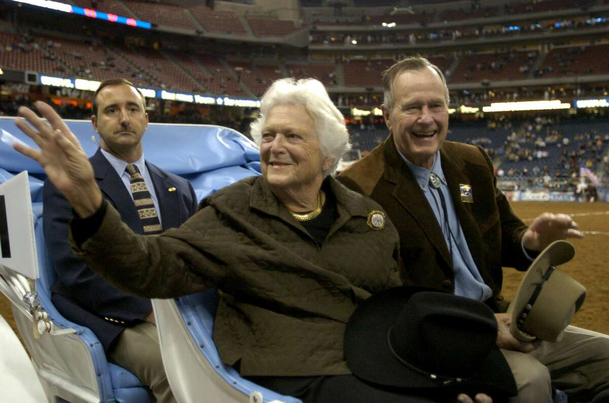 Former First Lady Barbara Bush, left, and former President George H.W. Bush ride in the grand parade during the opening performance of the Houston Livestock Show and Rodeo March 1, 2005, at Reliant Stadium in Houston. >> Keep clicking through this gallery to see Barbara and George's love story through photos.