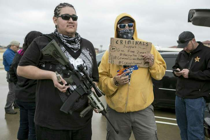 """Jimmy """"Freedom,"""" left, and Jason Orsek pose before they and other open-carry activists demonstrated and staged a mock shooting just outside the University of Texas campus in Austin, Dec. 12, 2015. Organizers had agreed not to go on campus after university officials warned them they would be trespassing if they did; a new state law will soon permit guns owners to bring them onto state campuses. (Ilana Panich-Linsman/The New York Times)"""