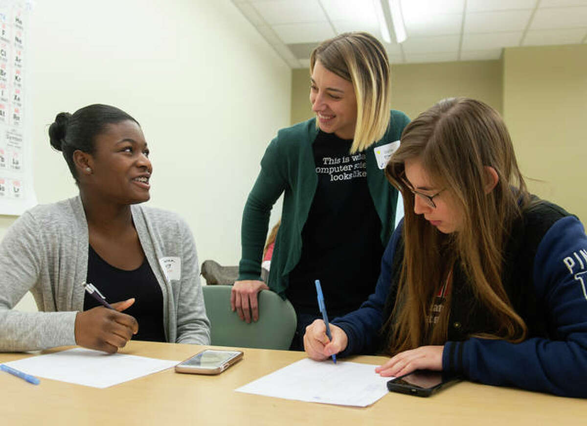 SIUE computer science alumna Darla Ahlert works with participants at SheCode 2018, including Breanna Goyea (left) from Governor French High School in Belleville, and Skylar Phenix (right), from Highland High School.