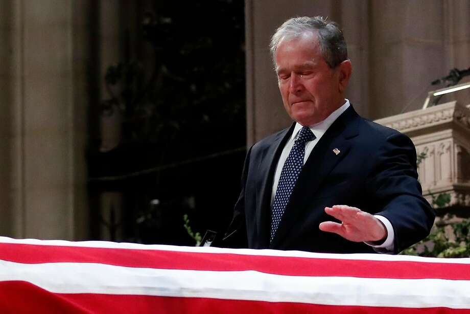 "Ex-President George W. Bush touches his father's coffin at the National Cathedral. ""To us,"" Bush said, ""his was the brightest of a thousand points of light."" Photo: Alex Brandon / AFP / Getty Images"