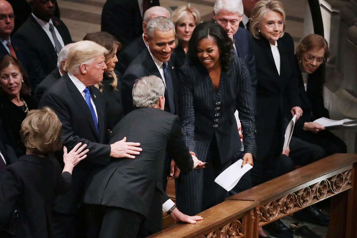 Former U.S. President George W. Bush leans across President Donald Trump and first lady Melania Trump to hand former first lady Michelle Obama what is likely a cough drop.
