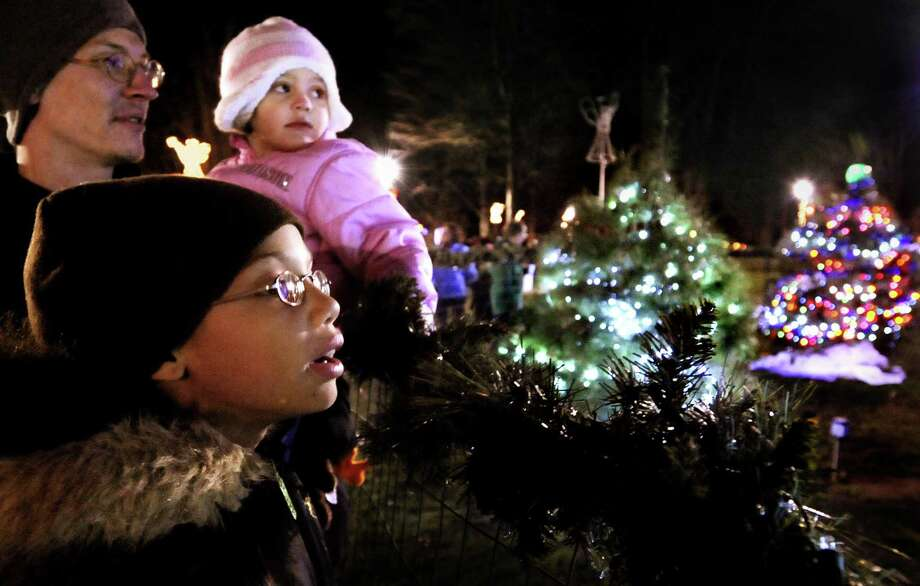 FILE PHOTO: Denise Lewis,9 (bottom) Shawn Belinda, and his daughter Alexyia Belinda,3, look over the newly lighted Christmas trees on the West Haven Green. Melanie Stengel/Register Photo: /