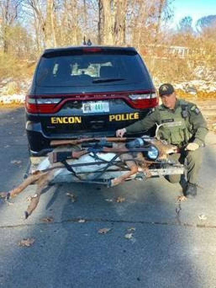 A state Department of Environmental Conservation officer poses with evidence seized during an investigation in to illegal hunting in Berne. Photo: State DEC