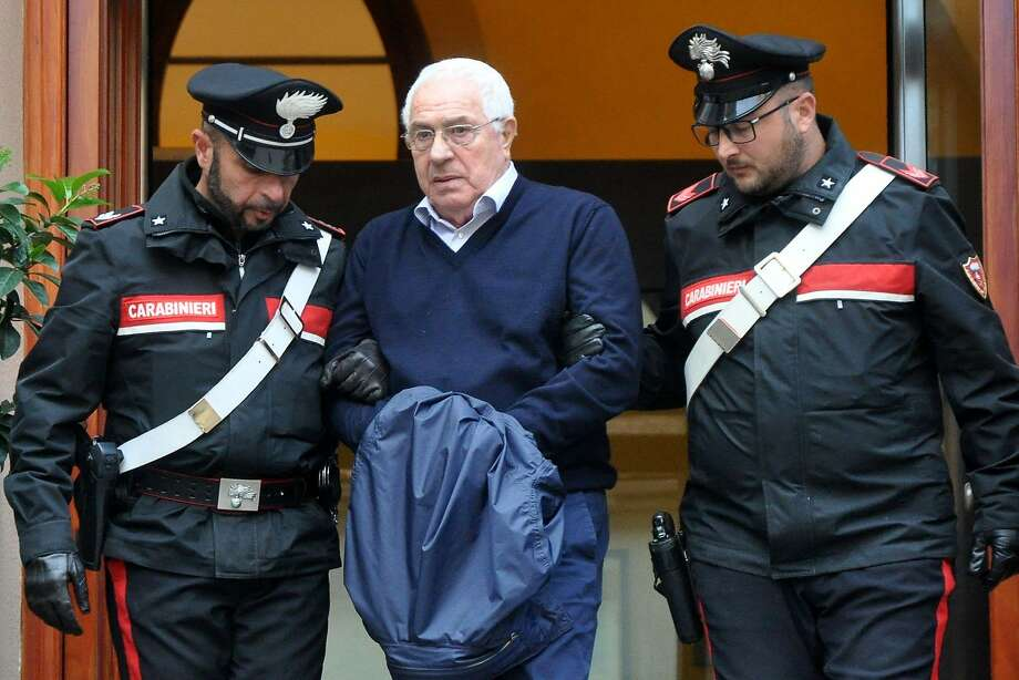 Settimino Mineo, the new head of the Sicilian mafia, is escorted by police after his arrest, in Palermo, Sicily. Wednesday's raids were against the powerful 'ndrangheta crime group. Photo: Alessandro Fucarini / AFP / Getty Images