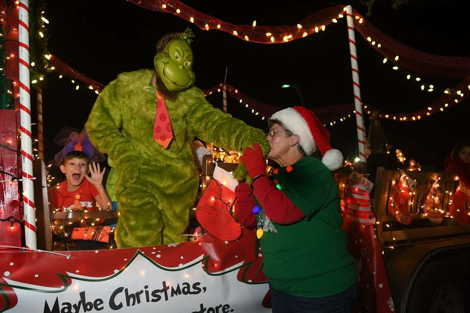 """Grinch"" Taylor Bacon, left, the Youth Director at the First United Methodist Church of Humble, gets a holiday greeting from fellow FUMC parishoner and float goer Jane McCary before the start of the 27th Annual Christmas Parade of Lights down Main Street in Humble on Dec. 4, 2018. The theme of this year's parade was ""How The Grinch Stole Christmas"". Photo: Jerry Baker, Houston Chronicle / Contributor / Houston Chronicle"