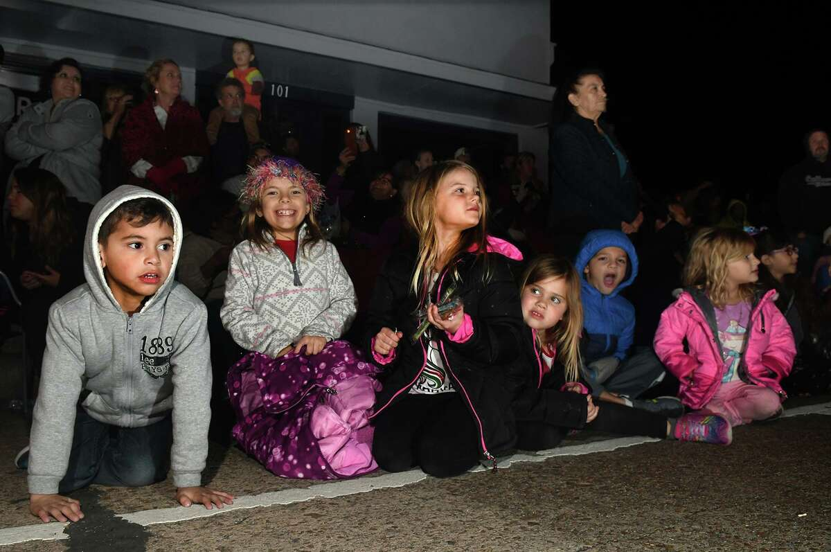 Manuel Gonzales, 5, from left, Kylie Looker, 8, Riley Johnsen, 8, Emma Johnsen, 5, Benjamin Denissen, 5, and Hannah Denissen, 5, take in the sights and sounds during the 27th Annual Christmas Parade of Lights down Main Street in Humble on Dec. 4, 2018. This year's parade theme was