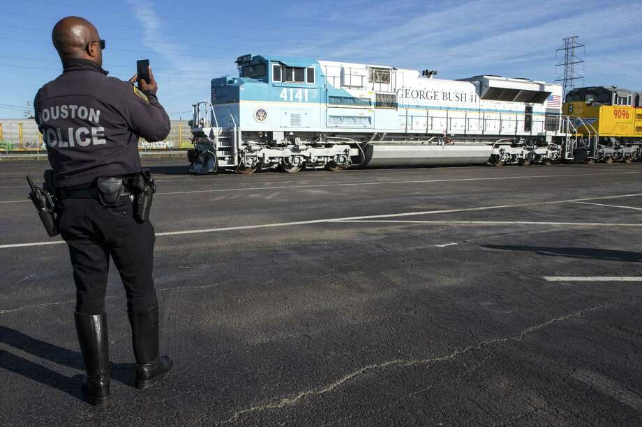 A Houston Police officer takes a photo of the Union Pacific 4141 George Bush 41 Locomotive as it is prepared for service on Dec. 3. UP 4141 will pull Union Pacific's passenger rail cars and the bagage car The Council Bluffs, which will carry former President George H.W. Bush's remains to College Station for burial. Photo: Brett Coomer, Houston Chronicle / Staff Photographer / © 2018 Houston Chronicle