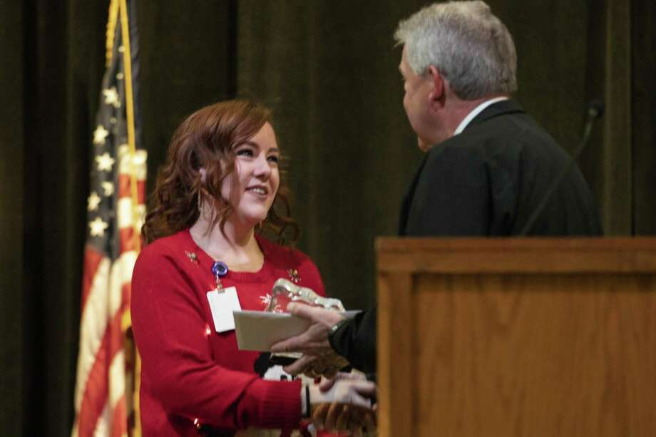 Taylor Nichols, forensic services, shakes hands County Judge Craig Doyal as she accepts the employee of the year award during the Montgomery County employees Annual Christmas Luncheon on Tuesday, Dec. 4, 2018 at The Lone Star Convention Center in Conroe. Photo: Cody Bahn, Houston Chronicle / Staff Photographer / © 2018 Houston Chronicle