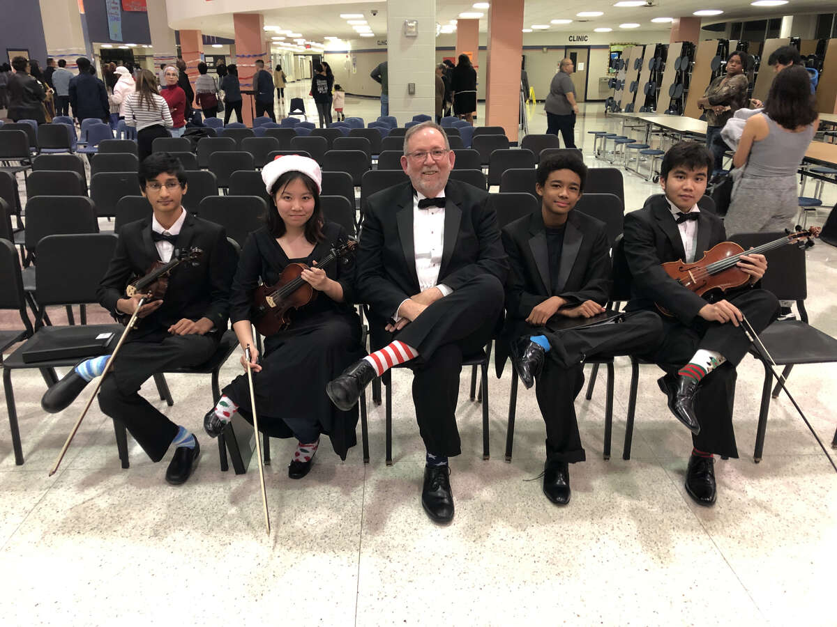 Shown with their crazy socks in honor of President Bush are (from left) Orchestra students Neel Jhangiani, Tiffany Nguyen, Director Brian Runnels, Anthony Duke and Brandon Musngi.