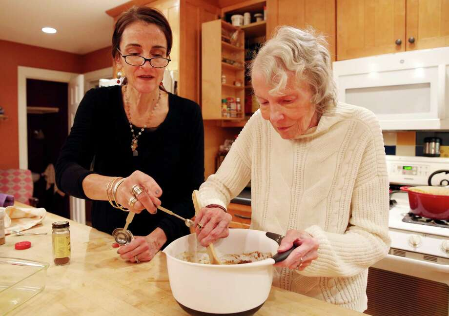 Caroline Barrett, left, and Lorretta S. Lewin mix together the ingredients for the 'Boozy Spiced Fig Cake' Thursday Nov. 29, 2018 at Caroline's home in Delmar. (Phoebe Sheehan/Special to the Times Union) Photo: Phoebe Sheehan