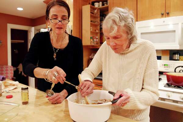 Caroline Barrett, left, and Lorretta S. Lewin mix together the ingredients for the 'Boozy Spiced Fig Cake' Thursday Nov. 29, 2018 at Caroline's home in Delmar. (Phoebe Sheehan/Special to the Times Union)