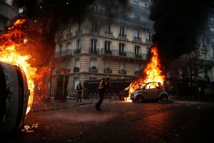 TOPSHOT - Protesters walk by burning cars during clashes with riot police on the sideline of a protest of Yellow vests (Gilets jaunes) against rising oil prices and living costs, on December 1, 2018 in Paris. (Photo by Abdulmonam EASSA / AFP)ABDULMONAM EASSA/AFP/Getty Images