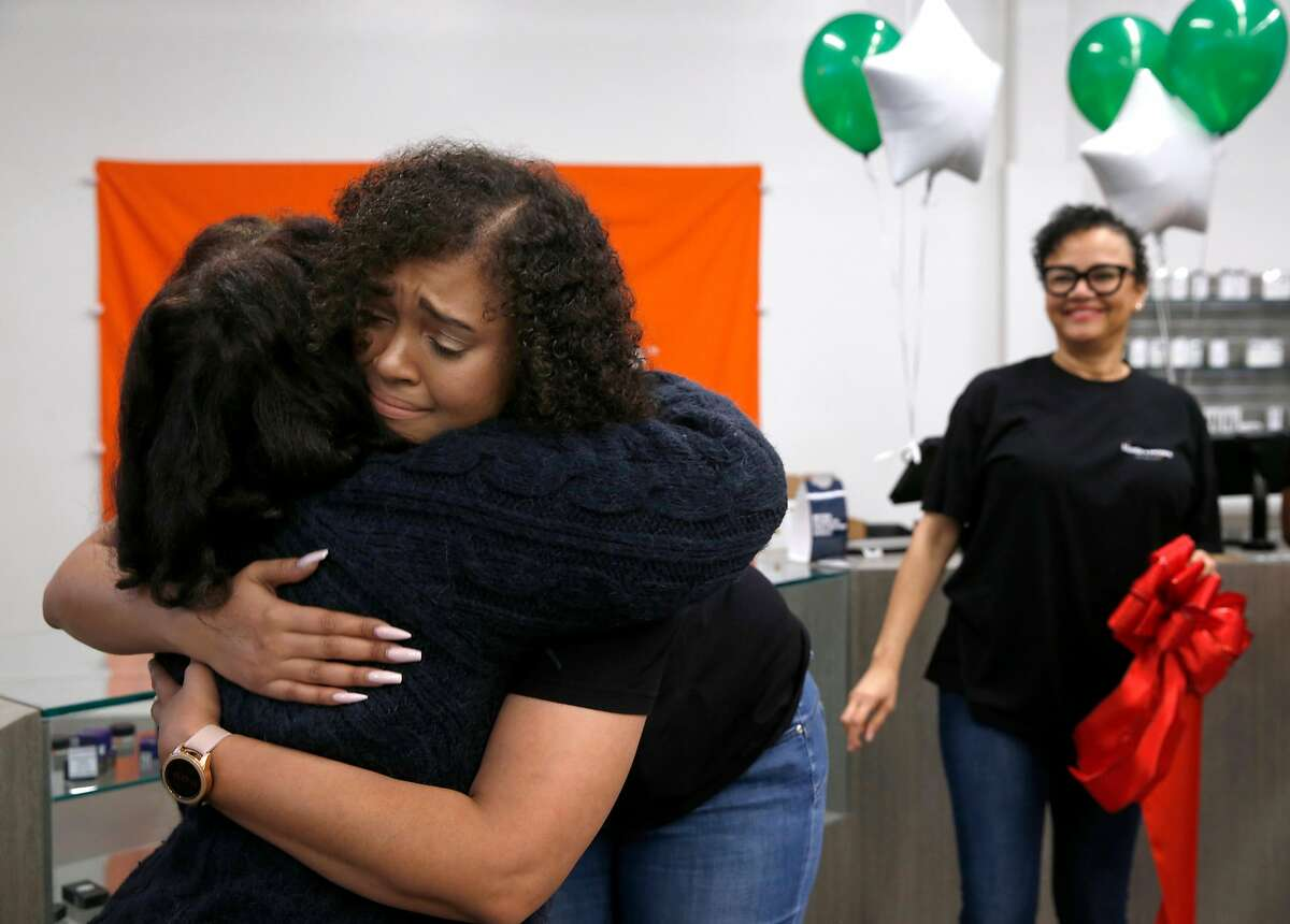 Brittany Moore hugs Desley Brooks (left) after the ribbon was cut to open the Blunts + Moore cannabis dispensary she co-owns with Alphonso Blunt in Oakland, Calif. on Thursday, Nov. 29, 2018, the first dispensary to open through the city's cannabis equity program. Watching at right is Brittany's mother Phae Moore.