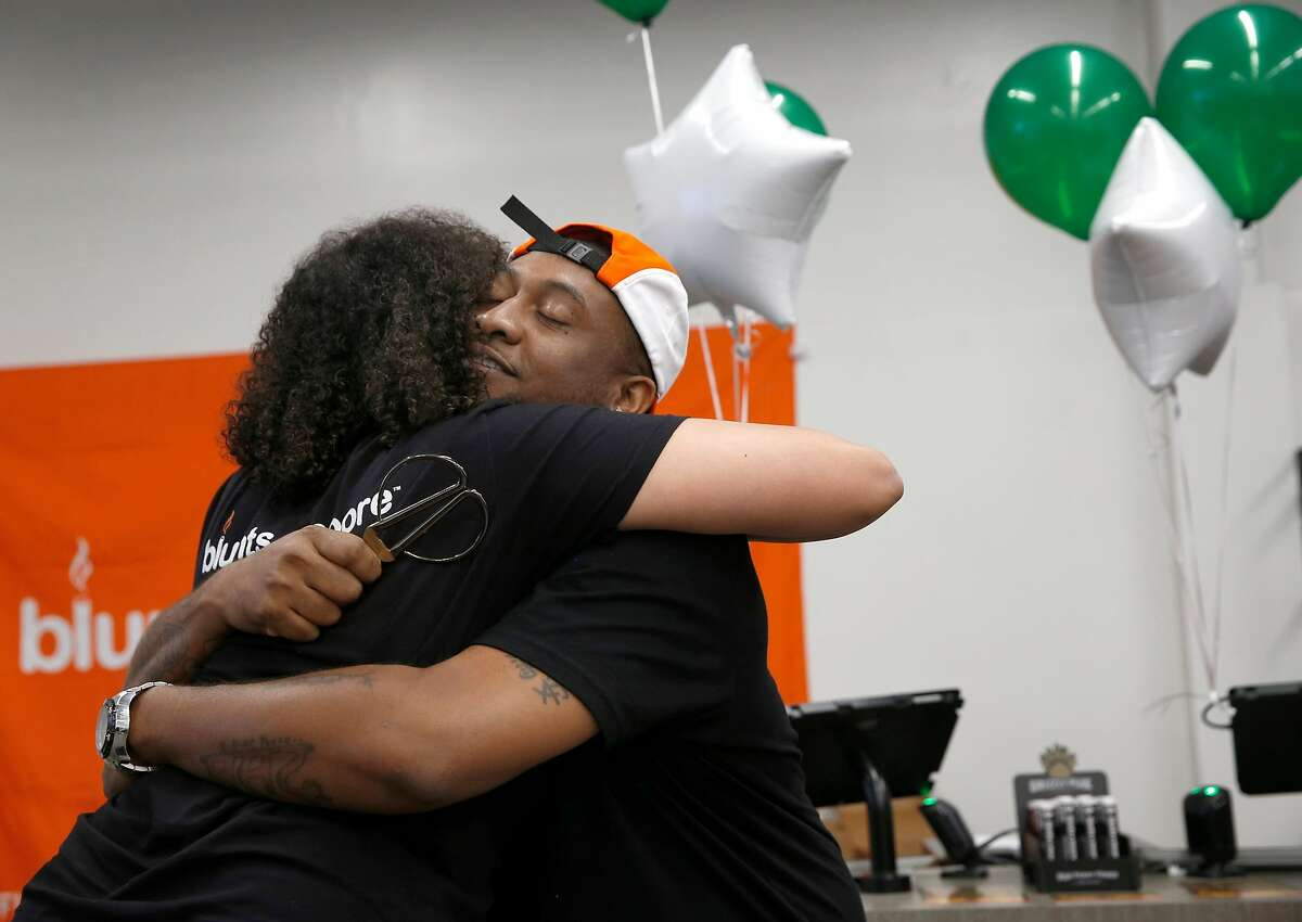 Alphonso Blunt hugs his business partner Brittany Moore after cutting the ribbon to open the Blunts + Moore cannabis dispensary in Oakland, Calif. on Thursday, Nov. 29, 2018, the first dispensary to open through the city's cannabis equity program.