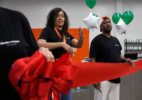 Brittany Moore and Alphonso Blunt get ready to cut the ribbon on their Blunts+Moore cannabis dispensary in Oakland. Photo: Paul Chinn / The Chronicle