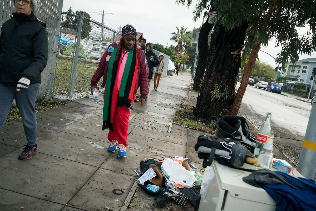 Nina Parker walks past a pile of discarded items near the Dignity Village homeless encampment in Oakland, Calif. on Wednesday, Dec. 5, 2018.