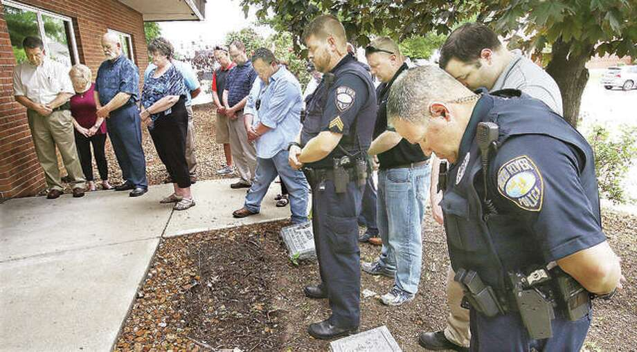 Wood River Police officers and city officials bow their heads during a prayer at a brief May ceremony held in front of the Wood River Police station to honor the two Wood River officers who have died in the line of duty over the years. The ceremony was part of National Police Week. Photo: John Badman | The Telegraph