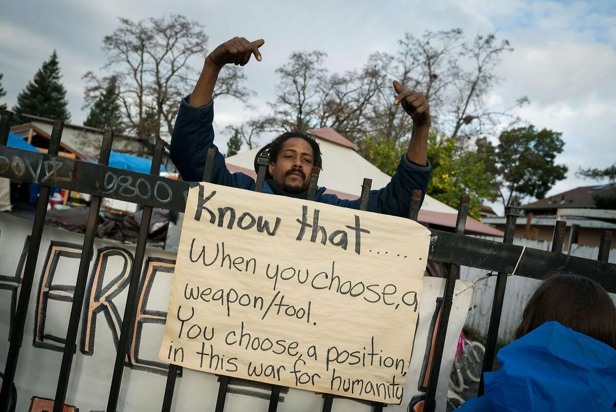 Ayat Jalal, 45, of Oakland, gestures to a sign taped on the fence at Dignity Village homeless encampment in Oakland, Calif. on Wednesday, Dec. 5, 2018.