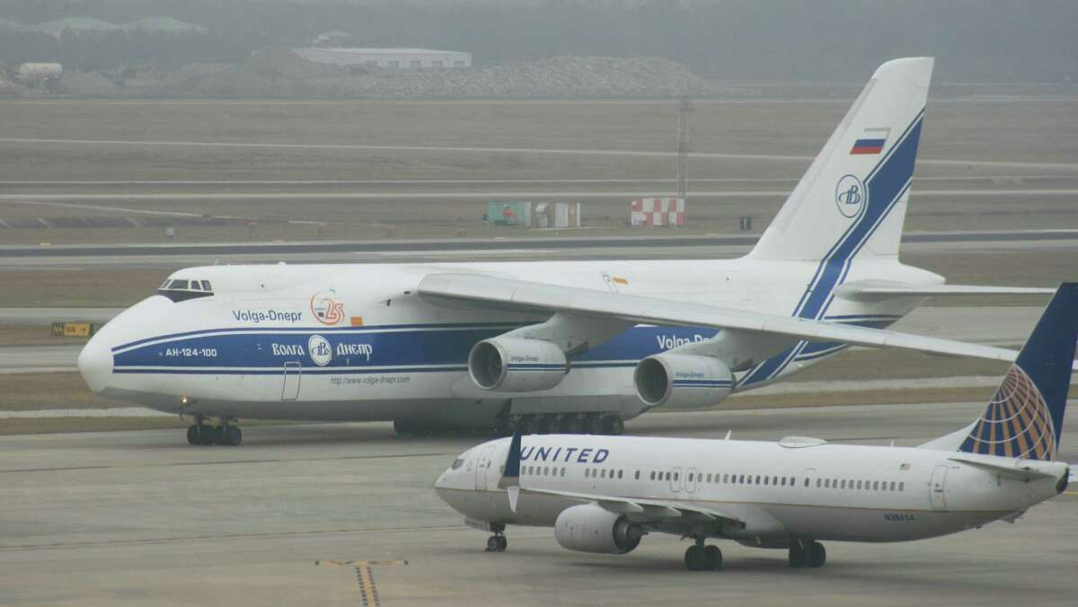 An Antonov AN-124 cargo plane passes near a United Airlines Boeing 737 at Bush Intercontinental Airport.