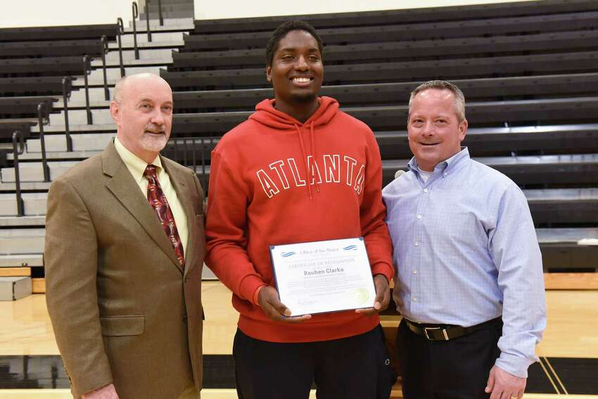 Troy Mayor Patrick Madden, left, and head coach Ralph Isernia, right, pose for a photo with Rensselaer Polytechnic Institute football player Reuben Clarke at RPI on Wednesday, Dec. 5, 2018 in Troy, N.Y. On November 21, after departing the Albany-Rensselaer Train Station, two train cars detached from the locomotive. Clarke, who witnessed the detachment, was hailed by other passengers as a hero for his quick actions to pull the emergency brake and stop the train. The mayor was recognizing the RPI football team on 2018 season. RPI won the Liberty League title and advanced to the quarterfinals of the NCAA Tournament in 2018. (Lori Van Buren/Times Union)