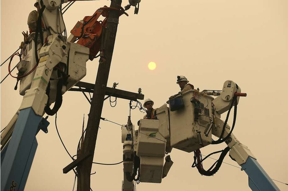 Pacific Gas and Electric crews work to restore power lines in Paradise in November after the deadly Camp Fire devastated the town. Photo: Rich Pedroncelli / Associated Press